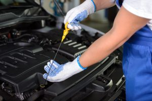 photo of worker checking car oil
